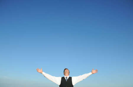 Businessman with arms open, blue sky. Above space for text or graphics.