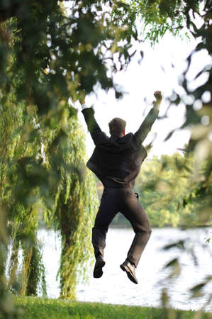 Young businessman jumping in a park. photo