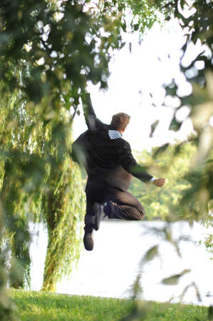 businessman jumping: Young businessman jumping in a park. Stock Photo