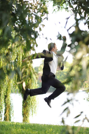Young businessman running in the park. photo
