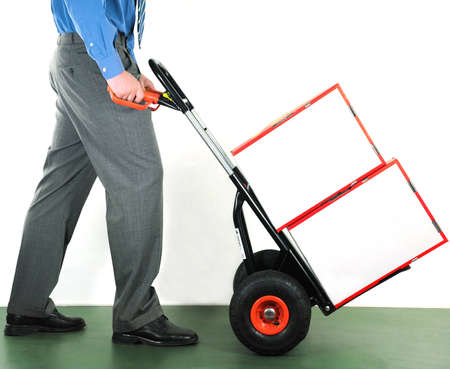 Businessman pushing a manual trolley. Two white blank boxes. photo