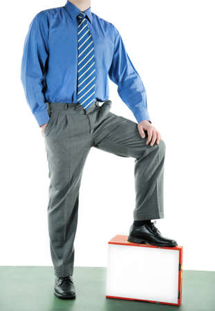Businessman with one white blank box standing on a green plattform. photo