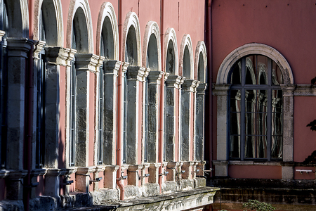 An array of arched windows and their image continued in the reflection on another window Stok Fotoğraf