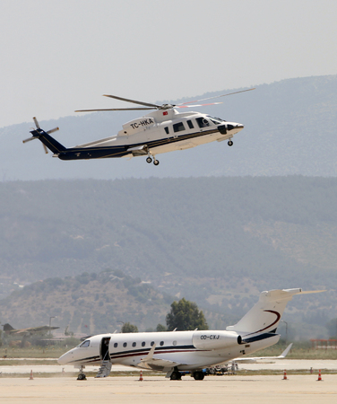 Bodrum, Mugla  Turkey - June 9th, 2018: A Sikorsky s-76c Spirit with tail no. TC-HKA lands next to an Embraer emb 550 legacy 500 business jet with tail no. OD-CXJ at Bodrum - Milas Airport.
