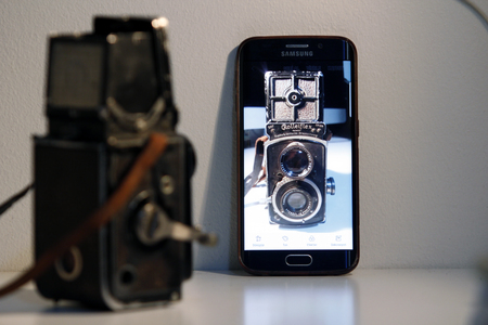 Istanbul, Turkey  January 26, 2019: A 1930 made Rolleiflex dual lens analogue camera stares at its own image on the digital display of Samsung smart phone screen side by side. Editorial