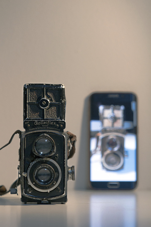Istanbul, Turkey  January 26, 2019: A 1930 made Rolleiflex dual lens analogue camera and image of the same camera on a Samsung smart phone screen side by side.