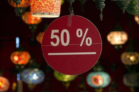 Close up image of a 50 % discount label with white text on red round cartoon ground in an oriental lamps shop with bokeh. Cheap tourism, retail, discount concepts.