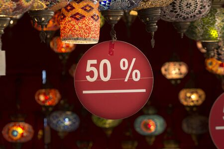 Close up image of a 50% discount label with white sans serif text on red flat cartoon hanging from a ceiling full of ornamental glass lamps in an interior. Concept for cheap tourism in the Mediterranean and the East.
