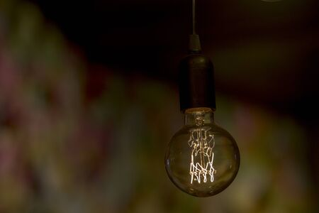 Close up image of a decorative retro light bulb shining weakly in dark room with strong bokeh in the background.