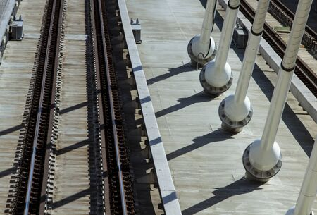 Empty metro rails on a suspension bridge over the Golden Horn at early morning, in high angle view image. A series of suspension cables' shadows cut through the rails.
