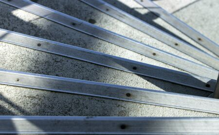 Close up high angle view of a series of concrete steps with protective metal bands at edges going down in a quarter spiral, under shadows and morning sun.