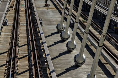 Two parallel lines of empty rail tracks on concrete ground are accompanied by a series of suspenders of the suspension bridge under harsh morning light. Shadows of suspenders cut through rails.