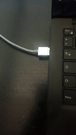 Opposites attract: white usb cable connects to black ultrabook.