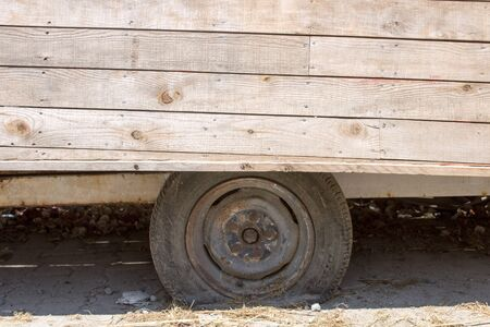 Close up of an unfinished wooden boat and the flat tire of a trailer, under sun. Problems of transportation concept.