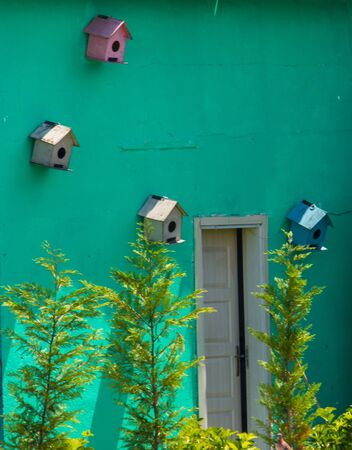 Four bird nests of alternating colors on a green wall with a door left open and some newly planted trees. Outdoor decoration concept. 스톡 콘텐츠