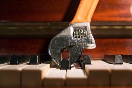 Close up of an adjustable wrench holding and pressing a piano key. Fine tuning concept.