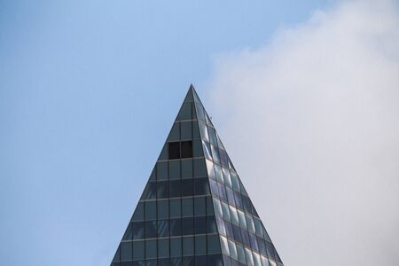 Sharp pointed peak of an office building tearing up the blue sky. Large copy space at top, left and right.