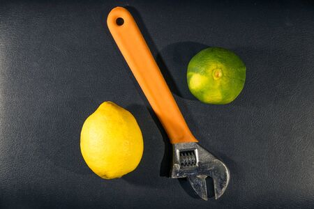 Top view of a lemon, a tangerine, and an adjustable wrench forming a percentage symbol on black leather background. Adjusting nutrient ingredients of a diet.