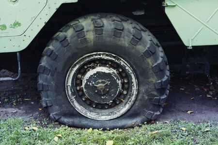 Close up of a flat tire of a heavy duty military vehicle on field.