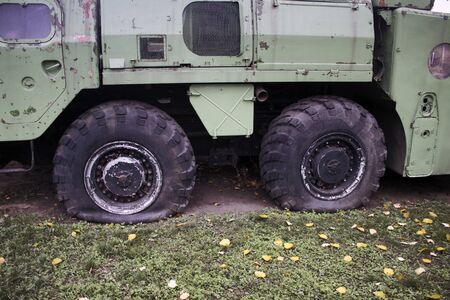 Close up of flat tires of a heavy duty military vehicle, for balistic missiles or air defence. Transport and logistics problems concept.