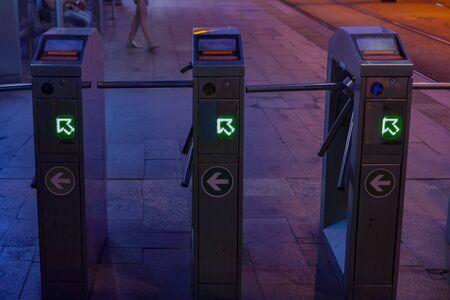 Three turnstiles of a street tram station by night waiting for few passengers, in vivid lights.