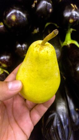 Close up of a males hand holding a yellowish fat pear, accompanied by deep purple egg-plants in the background.
