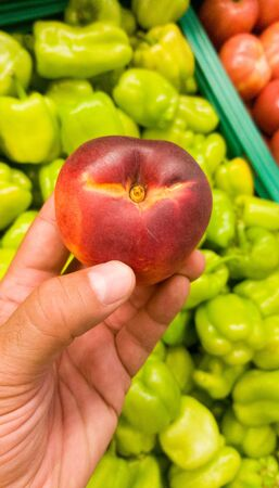 Close up of a male hand holding a nectarine fruit, with green sweet bellpeppers and tomatoes in the background.