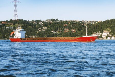 Landscape view of a red dry cargo ship at sea, passing by the Bosphorus.