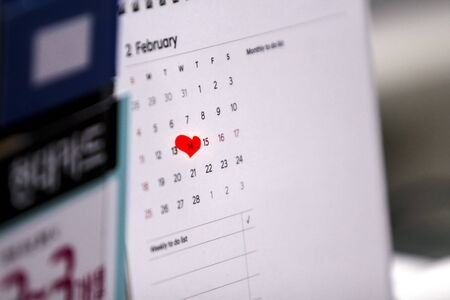 Close up of a desk calendars February page where Valentines Day is marked by an irregular red heart mark.