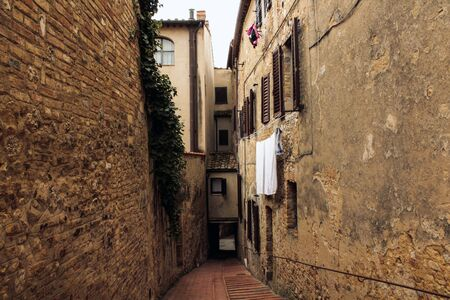 A narrow, brick walled medieval street in Italy with drying laundry hanging from a window in St. Gimignano, Italy. 免版税图像