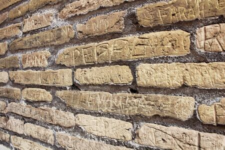Close up image of carved names on bricks of a historical wall at Rome, Italy. Concept for vandalism and effects of tourism.