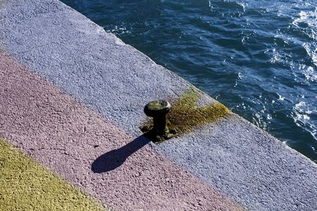 High angle view of a rusted bollard and its shadow elongated through alternating colors on the ground of a concrete covered port, with blue sea diagonally cutting the frame. Concept image for ambiguity, ambivalent situations; invasion of personal space