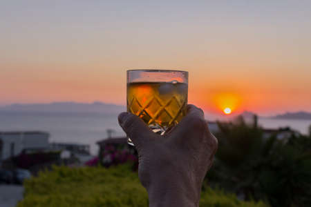 An elder woman's hand raises a glass of whiskey on the rocks against the sunset at the Aegean Sea, with islands in the background and green foliage in the middle ground. 免版税图像