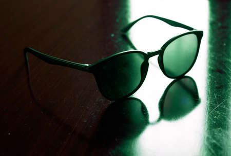 A pair of sunglasses backlit by strong natural light on scratched, dusty wooden surface. Eyewear care concept. 免版税图像