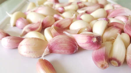 Close up of multiple garlic cloves in red and white skins on white background.