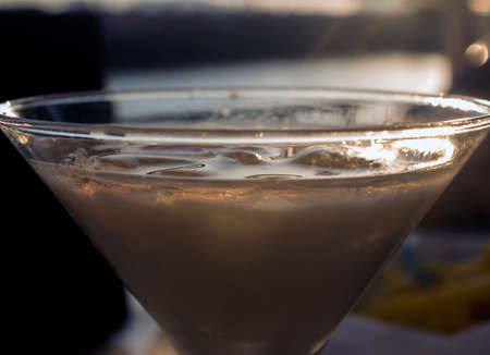 Close up detail image of cream alcohol drink on ice in V shaped cocktail glass. Sunset shot outdoors.