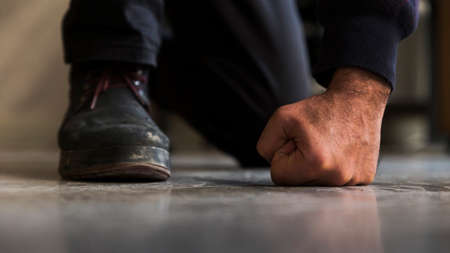 Close up detail of a crouched unrecognizable man's fist and foot with boot, standing on gray, screed floor in front shot.