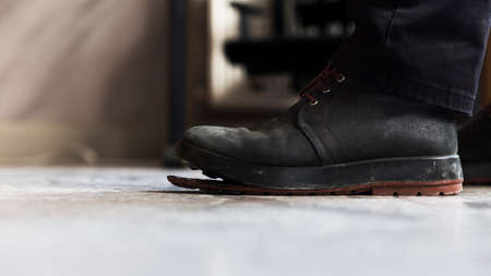 Central perspective low angle profile close up of a man's foot with a weathered nubuk boat with detached plastic sole, standing on screed floor.