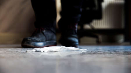 Close up low angle view image of the boots of a walking male, almost stepping on a white protective mask, abandoned on screed floor.