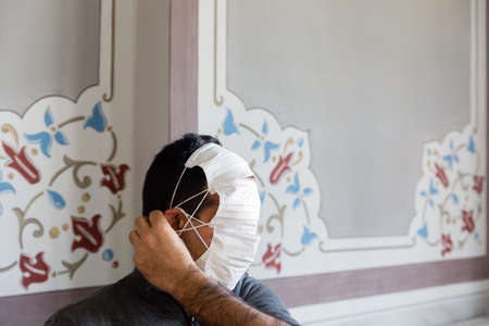 Profile of an unrecognizable man with multiple protective masks and his hand adjusting the straps on ear. Banque d'images