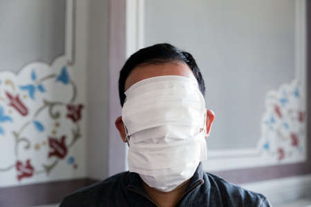 Unrecognizable adult man with short hair with his face fully covered by protective masks, in front central shot