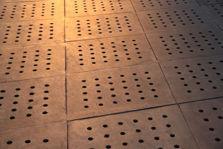 Concrete paving tiles with regular holes under tungsten light. Background image.