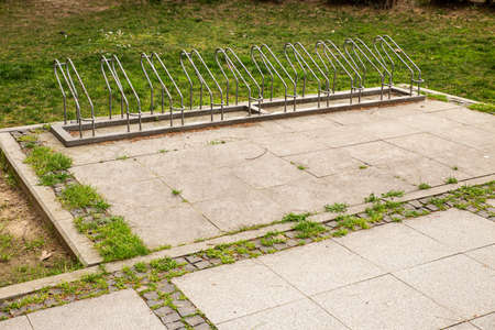 Empty bicycle park with steel slots on pavement next to green grass. 免版税图像