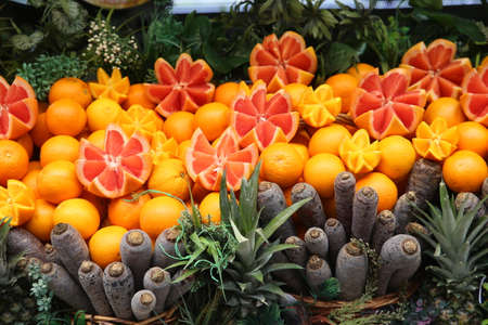 Full frame image of Grapefruits, oranges, red carrots and ananas on display at a fruit juice store's counter