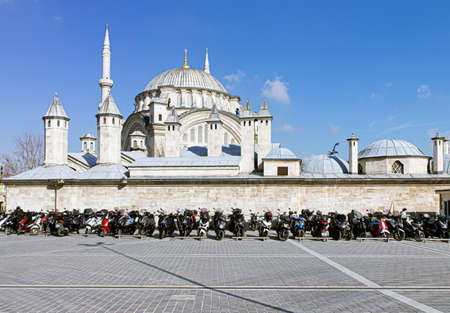 Cemberlitas, Istanbul Turkey - March 1st, 2021: Nuru Osmaniye Mosque, an example of Ottoman Baroque architecture and dozens of motorcycles parked in rows.
