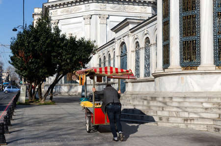 Fatih, Istanbul Turkey - March 1st, 2021: Empty streets in historical Istanbul with a corn vendor looking for customers in front of the Sultan Mahmud II Mausoleum, during the lockdown,