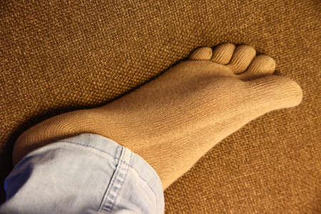 Healthy finger socks wearing foot on sofa in close up image showing the sole.