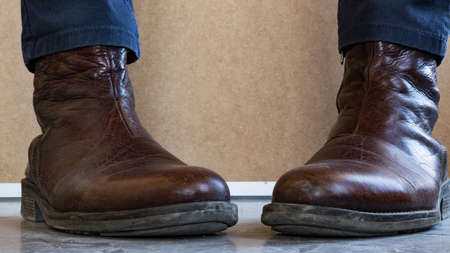 Close up of Leather boots wearing feet facing each other.