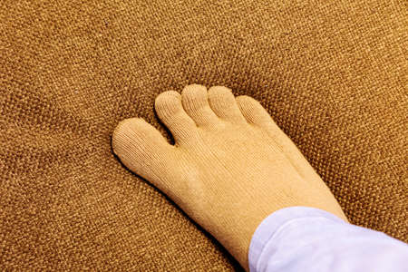 Healthy finger socks wearing foot on sofa in top view close up image. 免版税图像