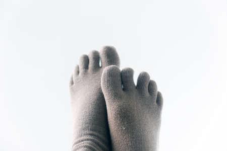 A couple of feet wearing finger socks, crossed, isolated on white background. 免版税图像